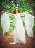 美丽的红头发人妇女佩带的白色礼服在庭院里 库存图片