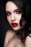 美丽的纵向妇女 摆在紧密在黑背景的小姐 魅力组成,红色唇膏 免版税库存照片