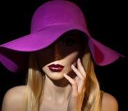 美丽的纵向妇女 艺术方式照片工作室 与淡紫色帽子的美好的年轻模型在色的背景,演播室射击 库存图片