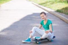 美丽的美丽的女孩在Longboard风景街道上的高速公路乘坐 太阳定调子 特写镜头画象 库存照片