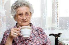 美丽的老妇人享受咖啡口味  免版税库存照片