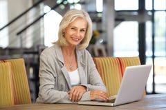美丽的老妇人运转的便携式计算机里面 免版税库存图片