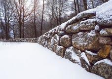 美丽的老石墙透视,有一个有薄雾的冬天森林的在背景中 库存照片