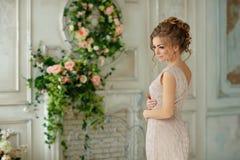 美丽的肉欲的女孩白肤金发在米黄礼服在轻轻地微笑 免版税库存图片