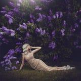 美丽的肉欲的女孩金发碧眼的女人在春天 春天样式 开花的日庭院可能反弹晴朗 金礼服的一个女孩说谎下 免版税图库摄影