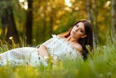 美丽的肉欲的深色的女孩画象白色礼服sitti的 免版税库存照片