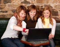 美丽的膝上型计算机学员三个年轻人 免版税库存图片