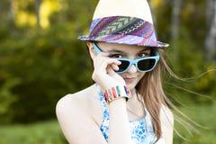 美丽的自然秀丽小女孩女小学生学生戴眼镜穿戴,新鲜明亮的晴朗的夏日户外 免版税图库摄影