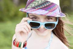 美丽的自然秀丽小女孩女小学生学生戴眼镜穿戴,新鲜明亮的晴朗的夏日户外 免版税库存图片