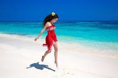 美丽的自由的少妇跳跃在异乎寻常的海的,浅黑肤色的男人s 免版税库存照片