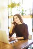 美丽的自由职业者女性研究线和谈话在电话和在家浏览在膝上型计算机或办公室 库存照片