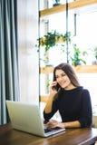 美丽的自由职业者女性研究线和谈话在电话和在家浏览在膝上型计算机或办公室 免版税库存照片