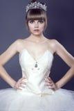 年轻美丽的芭蕾舞女演员画象站立用她的在臀部的手的珠宝水晶冠佩带的白色束腰和芭蕾舞短裙的 图库摄影