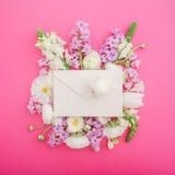 美丽的花和纸葡萄酒信封在桃红色背景 平的位置 顶视图 免版税图库摄影