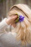 美丽的花在一名年轻白肤金发的妇女的手上白色羊毛衫的 第一朵春天花在森林里 免版税库存照片
