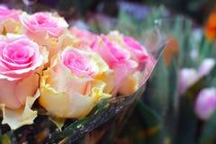 美丽的花束由与桃红色技巧的奶油色黄色玫瑰做成与模糊的花在背景中 免版税库存照片