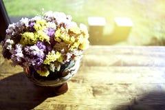 美丽的花瓶的软的焦点在一张木桌安置在与玻璃的一家咖啡店 免版税库存图片