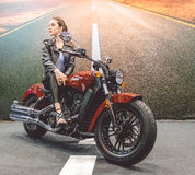 美丽的苗条女孩和一辆新的豪华摩托车 免版税库存图片