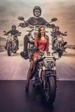 美丽的苗条女孩和新的豪华高速摩托车 免版税库存图片