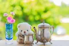 美丽的茶具和熊玩偶有花的在花瓶 库存图片