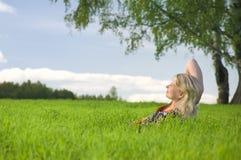 美丽的草松弛妇女年轻人 免版税库存图片