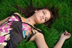 美丽的草绿色位于的妇女年轻人 免版税库存照片