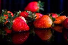美丽的草莓在黑背景中 库存图片