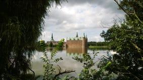 美丽的菲特列堡城堡在丹麦 在框架树和灌木一片平静的湖和叶子  库存图片