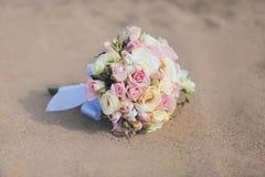 美丽的葡萄酒婚礼花束开花玫瑰沙子海滩 免版税库存照片