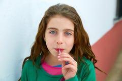 美丽的蓝眼睛哄骗吃棒棒糖甜点的gils 免版税库存照片