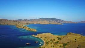 美丽的蓝色与少量的惊人的小山围拢的海滩和蓝天小船 免版税库存图片