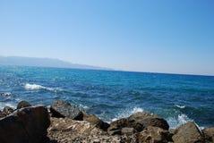 美丽的蓝色海和嬉戏的波浪在天空蔚蓝下 免版税库存照片