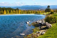 美丽的蓝色湖、树、房子和山 图库摄影