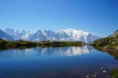 美丽的蓝色湖在欧洲阿尔卑斯,有勃朗峰的在背景中 库存照片
