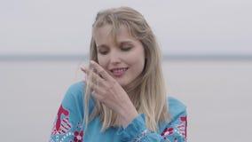 美丽的蓝色长的夏天礼服的可爱的年轻白肤金发的女孩有接触她的头发的刺绣的 时尚的概念 股票录像