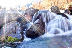 美丽的蓝色高山瀑布在有太阳火光的山森林里 免版税库存图片