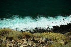 美丽的蓝绿色海波浪碰撞反对黑岩石 图库摄影