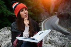 美丽的行家和读在山的旅行女孩一本书 库存图片