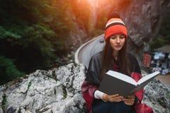 美丽的行家和读在山的旅行女孩一本书 免版税库存照片