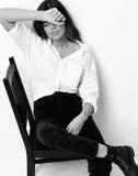 年轻美丽的行家女孩坐椅子在白色shi疲倦了 库存图片