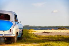美丽的被恢复的同色而浓淡不同的葡萄酒美国汽车停放了接近在古巴的南部的一个热带海滩 库存照片