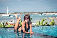 美丽的被晒黑的妇女画象放松在游泳池温泉的黑游泳衣的 热的夏日和明亮晴朗 图库摄影