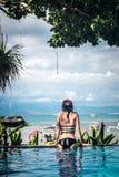 美丽的被晒黑的妇女画象放松在游泳池温泉的黑游泳衣的 热的夏日和明亮晴朗 库存图片