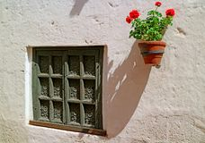 美丽的被雕刻的木窗口和一个赤土陶器大农场主与垂悬在白色外壁,阿雷基帕,秘鲁上的红色花 库存图片