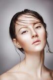 年轻美丽的裸体妇女画象有湿光亮的构成的在灰色背景 免版税库存照片