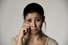 年轻美丽的西班牙哀伤的妇女严肃和关心的哭泣的感觉的沮丧的被隔绝的灰色 库存图片