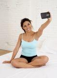 美丽的西班牙在拿着手机的床上的妇女微笑的愉快的开会拍自画象selfie照片 免版税图库摄影