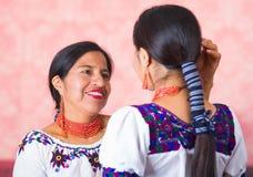 美丽的西班牙穿传统安地斯山的衣物的母亲和女儿,看见从面对的外形角度 免版税库存照片