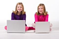美丽的计算机女孩双胞胎工作 免版税图库摄影