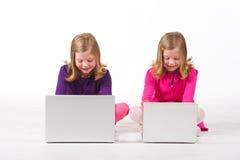 美丽的计算机女孩双胞胎工作 免版税库存照片